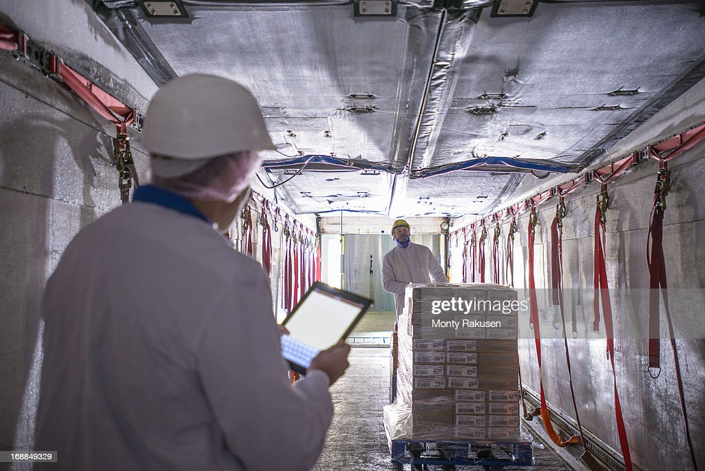 Worker checking products into freezer truck of food factory with tablet