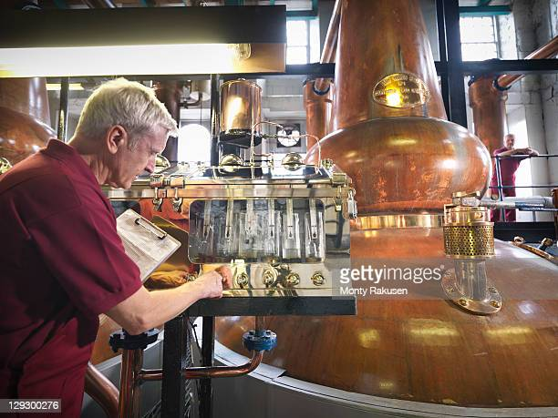 Worker checking pure whisky pouring from the stills in distillery