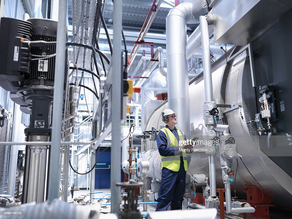 Worker checking readings on digital tablet in gas fired power station