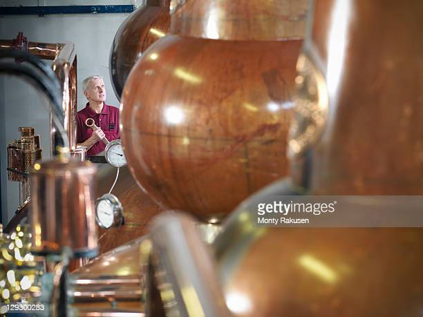 Worker checking whisky stills in distillery