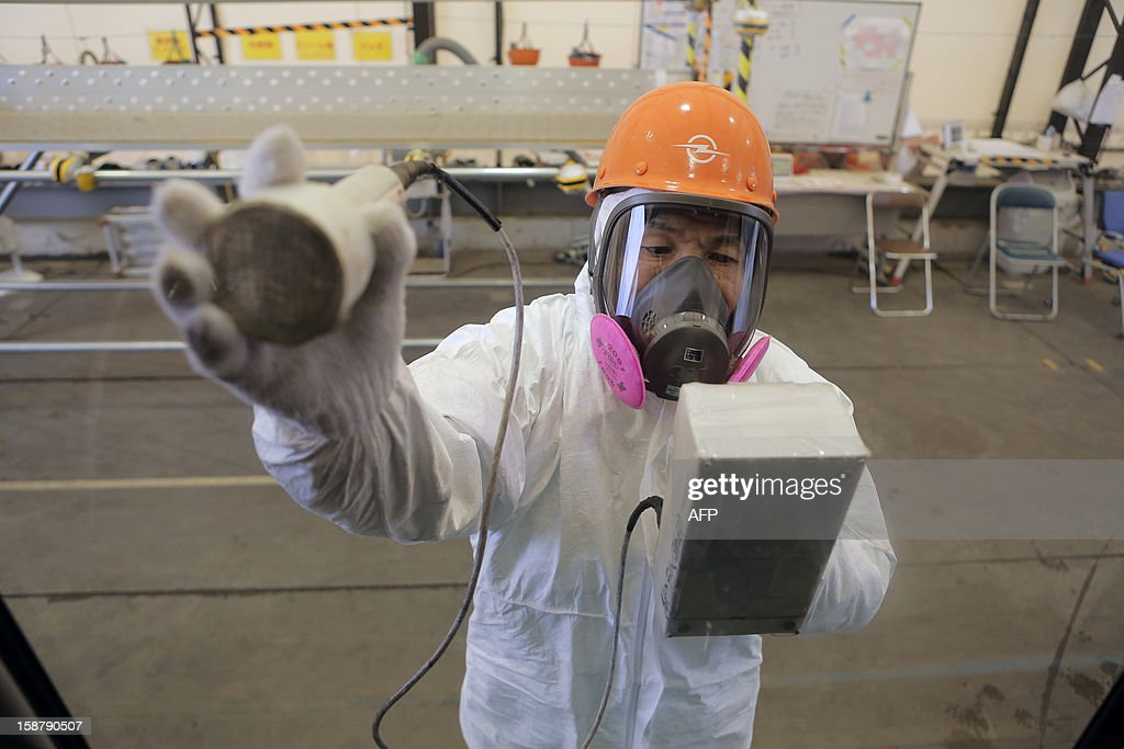 A worker checks a bus at the crippled Fukushima Daiichi Nuclear power plant in Ota on December 29, 2012. The clean-up at Fukushima after its tsunami-sparked nuclear meltdowns is an 'unprecedented challenge' Japan's prime minister Shinzo Abe told workers during a tour of the plant. AFP PHOTO / Itsuo Inouye / POOL