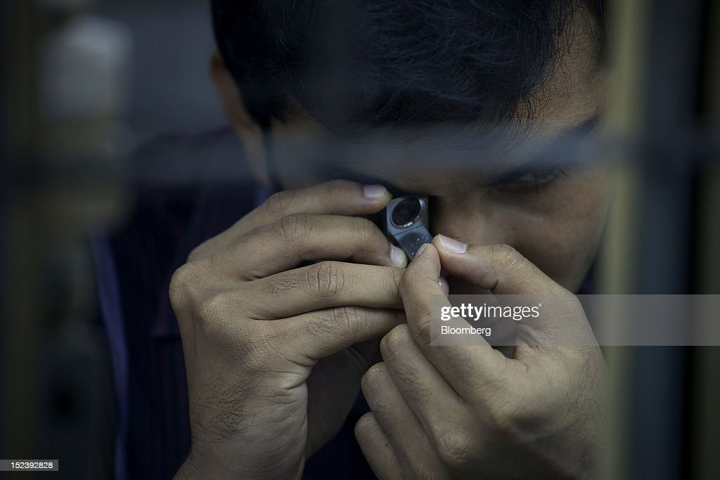 A worker checks a diamond through a magnifying glass inside a diamond cutting and polishing workshop in Mumbai, India, on Monday, Sept. 17, 2012. Sales of diamond jewelry in India are set to rise 16 percent annually in the five years to 2015, twice as fast as the 7 percent growth predicted for adornments made of the yellow metal, according to a study by New Delhi-based consultants AM Mindpower Solutions. Photographer: Adeel Halim/Bloomberg via Getty Images