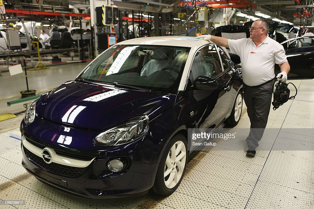 A worker checks a finished Opel Adam car at the assembly line shortly after a celebration to mark the launch of the new Opel compact car at the Opel factory on January 10, 2013 in Eisenach, Germany. Opel employees hope the car will help the compny return to profits after years of sagging sales and the announcement of the Bochum factory closure in 2016.