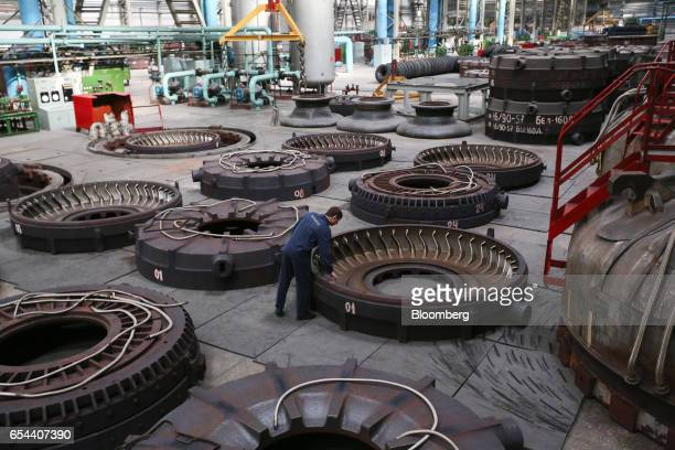 A worker checks a giant mould used to shape superoversized tires at the Belshina JSC tire factory in Babruysk Belarus on Thursday March 16 2017...