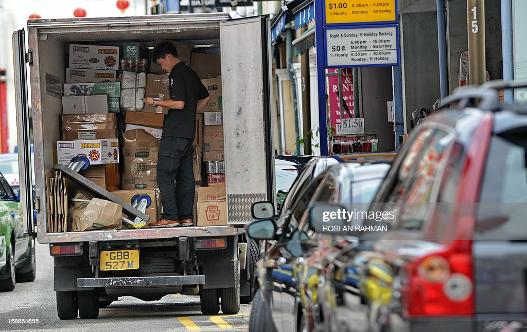 A worker checks a provision list before delivering supplies to a shop in Singapore on January 2, 2013. Singapore's economy grew in the fourth quarter, avoiding a technical recession despite disappointing growth figures for 2012, government data showed on January 2.