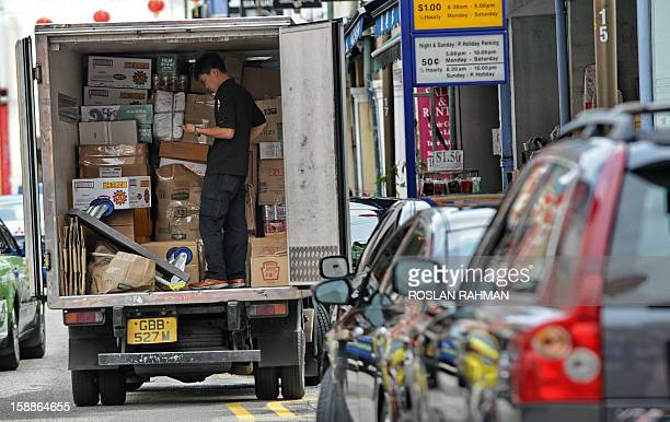 A worker checks a provision list before delivering supplies to a shop in Singapore on January 2 2013 Singapore's economy grew in the fourth quarter...
