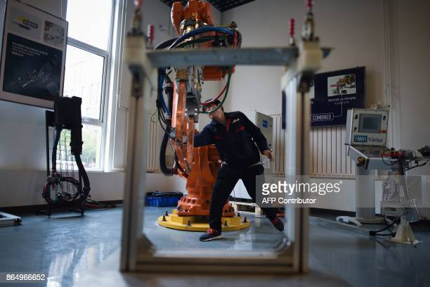 A worker checks a robot arm at a robot company during a tour arranged by the press center for the 19th Communist Party Congress in Xianghe county in...