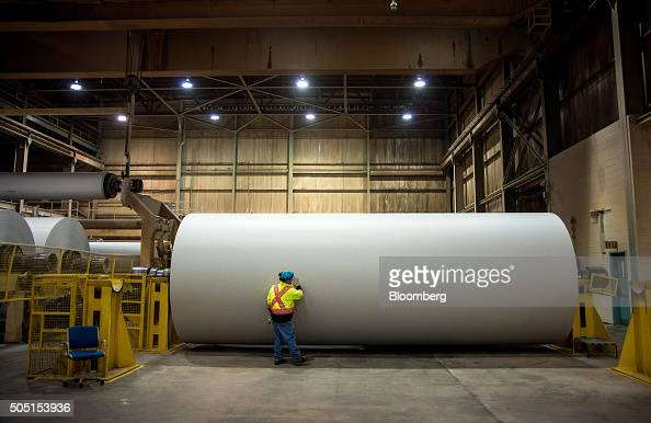 A worker checks a roll finished roll of newsprint paper weighing close to four tons on the production line at the Resolute Forest Products mill in...