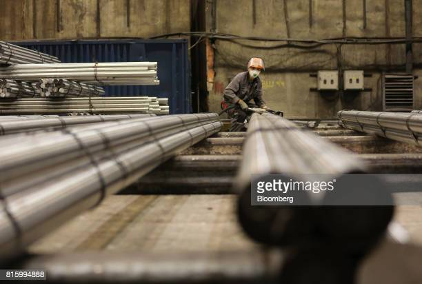 A worker checks and secures lengths of rolled steel rods ahead of distribution at the Oskol Elektrometallurgical Plant steel mill operated by...