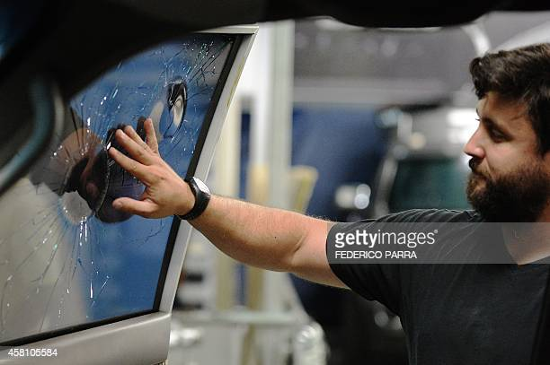 A worker checks armored windows of a car shot with bullets in a garage of armoured cars in Caracas on October 21 2014 With designer clothes...