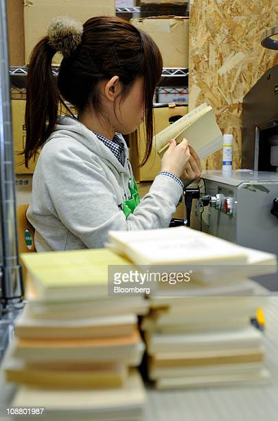 A worker checks books that have been cut for scanning at the offices of Bookscan in Tokyo Japan on Monday Dec 27 2010 Japan's cramped living...