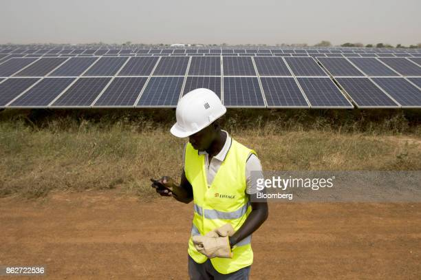 A worker checks his mobile phone during an inspection of photovoltaic solar panels at the Senergy Santhiou Mekhe PV solar plant in Thies Senegal on...