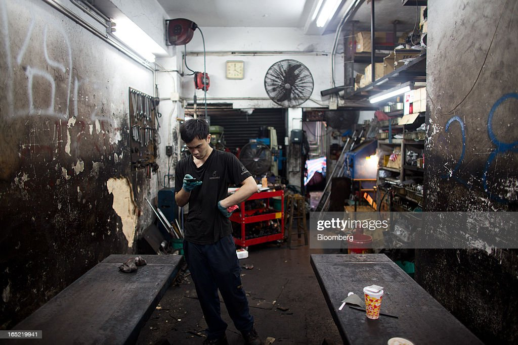 A worker checks his mobile phone inside a car-repair shop in the Tai Hang area of Hong Kong, China, on Saturday, March 30, 2013. Rents are climbing in neighborhoods near Causeway Bay and Hong Kong's other prime shopping districts, known for luxury stores that attract free-spending tourists from mainland China. That's squeezing out mom-and-pop shops, congee and noodle vendors as developers and landlords seek to profit from the trend. Photographer: Lam Yik Fei/Bloomberg via Getty Images