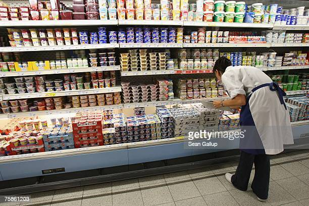 A worker checks inventory of yogurt containers on a supermarket shelf July 30 2007 in Berlin Germany German milk producers have announced they will...