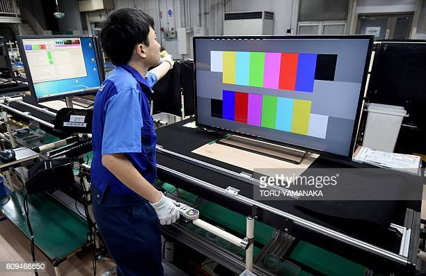 A worker checks LCD 4K televisions on an assembly line at the Utsunomiya Plant of Japan's electronics giant Panasonic in Utsunomiya 100 kilometres...