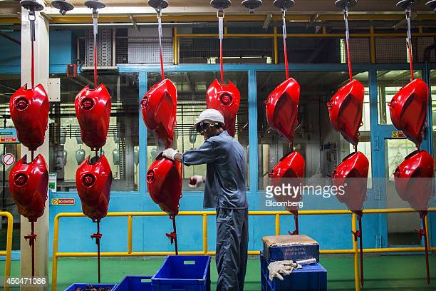 A worker checks recently sprayed gas tanks outside the paint shop at the Hero MotorCorp Ltd manufacturing facility in Gurgaon India on Wednesday June...