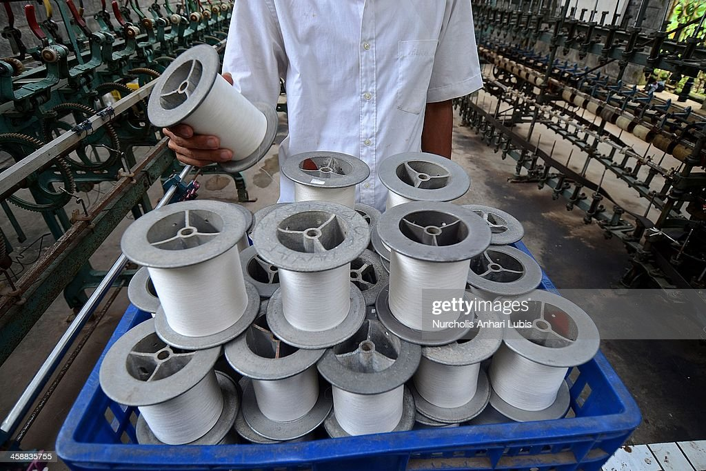 A worker checks spools of silk thread at a production unit on December 21, 2013 in Bogor, Indonesia. The Indonesian silk industry is well established although generally consisting of small and local producers in contrast to more developed competition and industry seen in countries such as Japan, China and Thailand. The silk produced is used in the manufacture of traditional handicrafts including batik clothing and textiles.