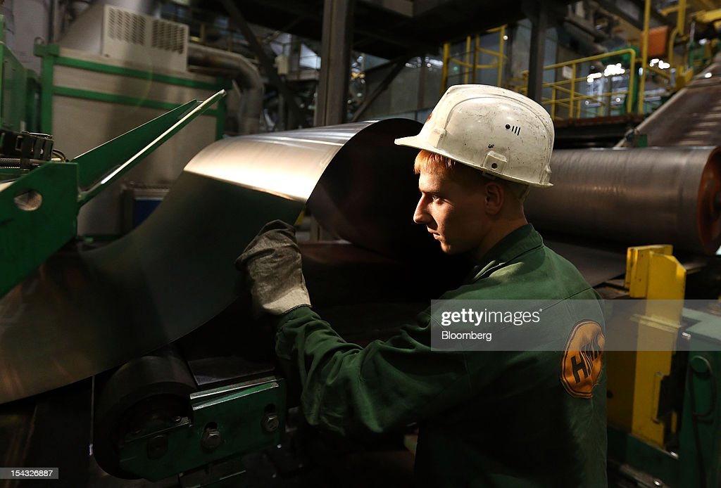 A worker checks steel sheet as it passes through a rolled steel module at the OAO Novolipetsk Steel plant, also known as NLMK, in Lipetsk, Russia, on Wednesday, Oct. 17, 2012. OAO Novolipetsk Steel, controlled by billionaire Vladimir Lisin, became Russia's largest steelmaker by output after boosting production by 24 percent. Photographer: Andrey Rudakov/Bloomberg via Getty Images