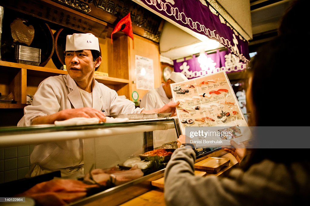 A worker checks stock of fish with a colleague as he prepares to serve Sushi at the Tsukiji fish market on February 28 2012 in Tokyo Japan Handling...