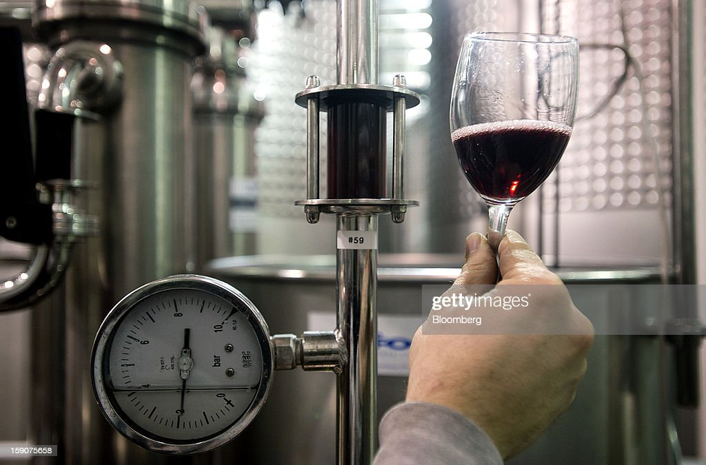 A worker checks the color of a red wine in a glass after going through the filtration system at the Ferrante Winery in Geneva, Ohio, U.S., on Friday, Jan. 4, 2013. Ice wine is a type of dessert wine produced from grapes that have been frozen while still on the vine, because the sugars and other dissolved solids do not freeze, but the water does, this allows a more concentrated grape must to be pressed. Photographer: Ty Wright/Bloomberg via Getty Images