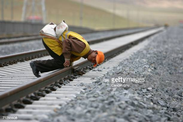 A worker checks the DangxiongLhasa section of the QinghaiTibet Railway on June 25 2006 in Dangxiong County of Lhasa Tibetan Autonomous Region China...