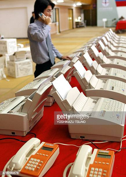 A worker checks the line on dozens of fax machines at Taiwan's Central Election Committee headquarters in Taipei 19 March 2004 a day before the...