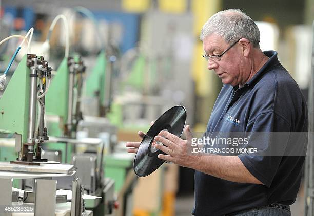 A worker checks the quality of a vynil on a production line at the MPO International company the last French manufacturer in Averton western France...