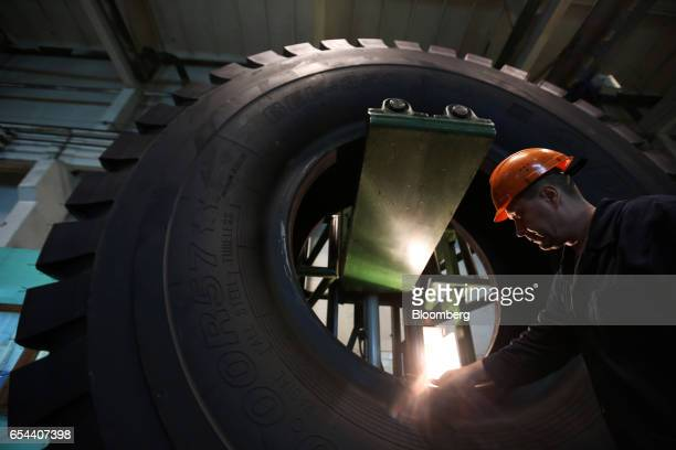 A worker checks the rim of a large 4000R57 sized tire in the control room at the Belshina JSC tire factory in Babruysk Belarus on Thursday March 16...
