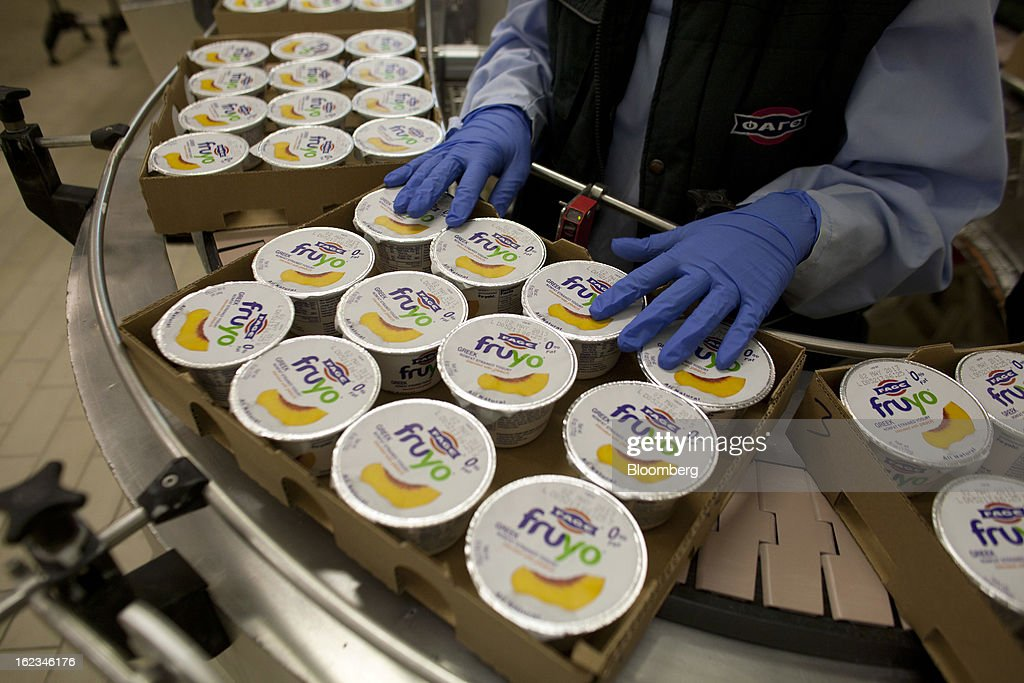 A worker checks trays of Fruyo peach-blended Greek yoghurt cartons as they pass along the production line during manufacture at the Fage Dairy Industry SA plant in Athens, Greece, on Thursday, Feb. 21, 2013. An October restructuring that placed Fage International SA's Greek units in a subsidiary called Fage Dairy Industry SA coincided with Coca-Cola Hellenic Bottling SA's plan to flee the epicenter of Europe's debt crisis by moving its main stock listing to London from Athens. Photographer: Kostas Tsironis/Bloomberg via Getty Images