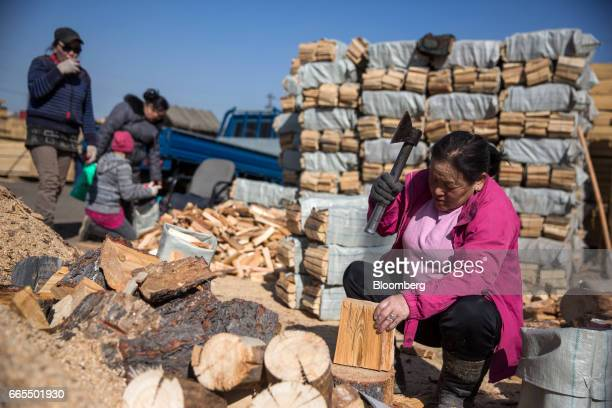 A worker chops wood with an axe at a timber supplier in Ulaanbaatar Mongolia on Tuesday March 14 2017 The subzero winters in Ulaanbaatar force...
