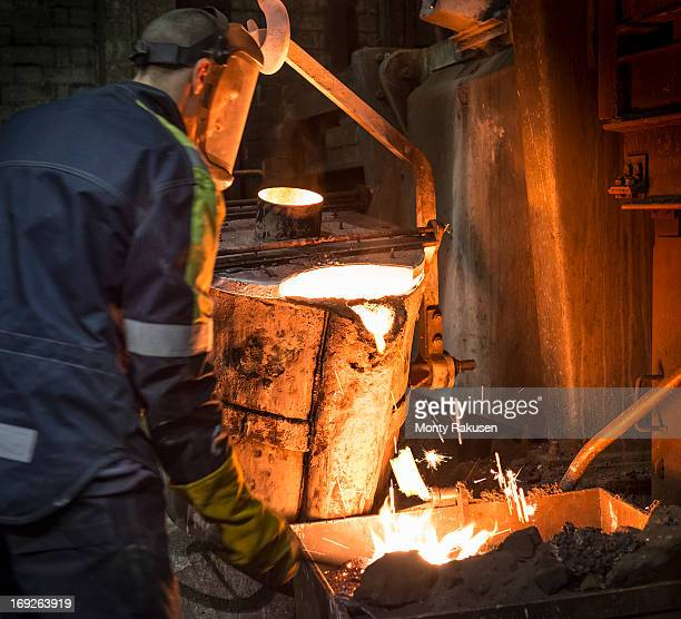 Worker cleaning and preparing surface of molten metal in foundry