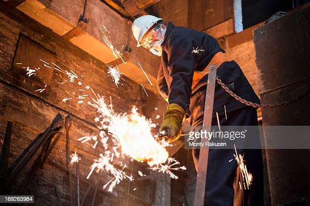 Worker cleaning surface of molten metal in foundry
