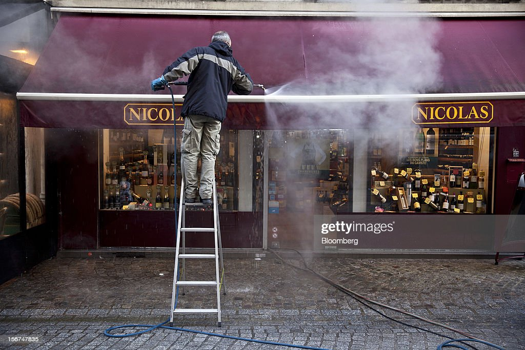 A worker cleans a canopy with a pressure washer outside the Nicolas wine store in Paris, France, on Tuesday, Nov. 20, 2012. France's government bonds fell, with 10-year yields rising the most in a month, after Moody's Investors Service lowered the nation's top credit rating, citing a worsening economic growth outlook. Photographer: Balint Porneczi/Bloomberg via Getty Images