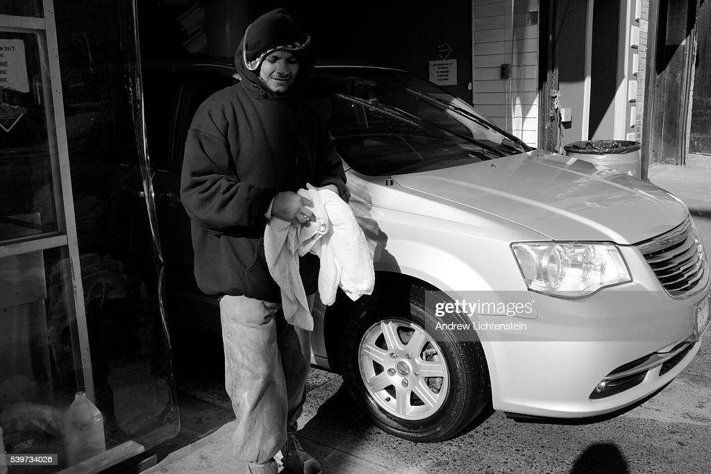 A worker cleans a car despite other car wash workers on strike who have formed a picket line to discourage drivers to use Sunny Day Car Wash in the...