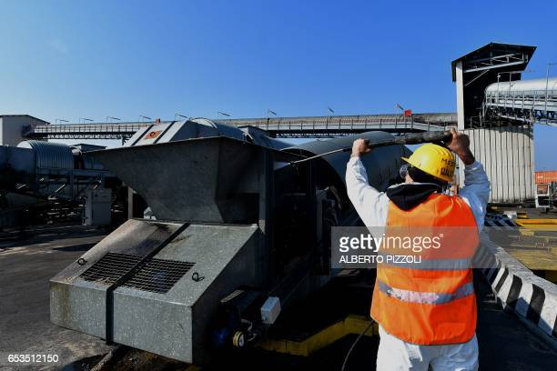 A worker cleans a conveyor belt at the commercial dock of French sugar cooperative Cristal Union after sugar was unloaded at the SFIR Raffineria di...