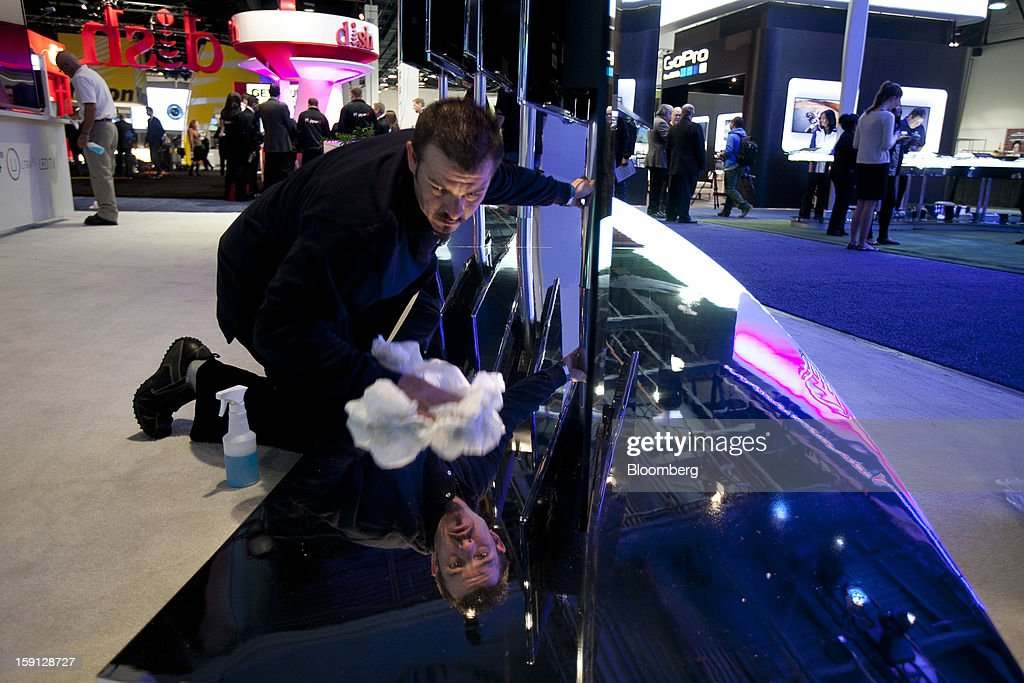 A worker cleans a display at the Hisense Electric Co. Ltd. booth during the 2013 Consumer Electronics Show in Las Vegas, Nevada, U.S., on Tuesday, Jan. 8, 2013. The 2013 CES trade show, which runs until Jan. 11, is the world's largest annual innovation event that offers an array of entrepreneur focused exhibits, events and conference sessions for technology entrepreneurs. Photographer: Andrew Harrer/Bloomberg via Getty Images