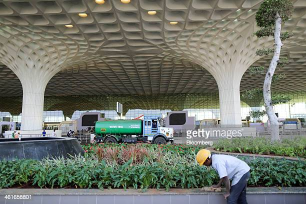A worker cleans a garden wall as a truck delivers water outside the newly built Terminal 2 of the Chhatrapati Shivaji International Airport operated...
