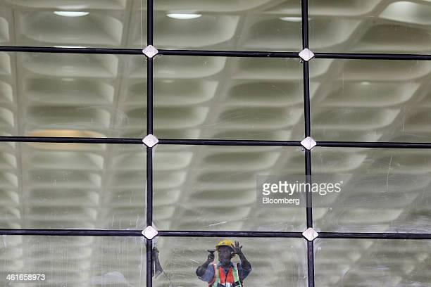 A worker cleans a glass interior wall of the newly built Terminal 2 of the Chhatrapati Shivaji International Airport operated by GVK Power...