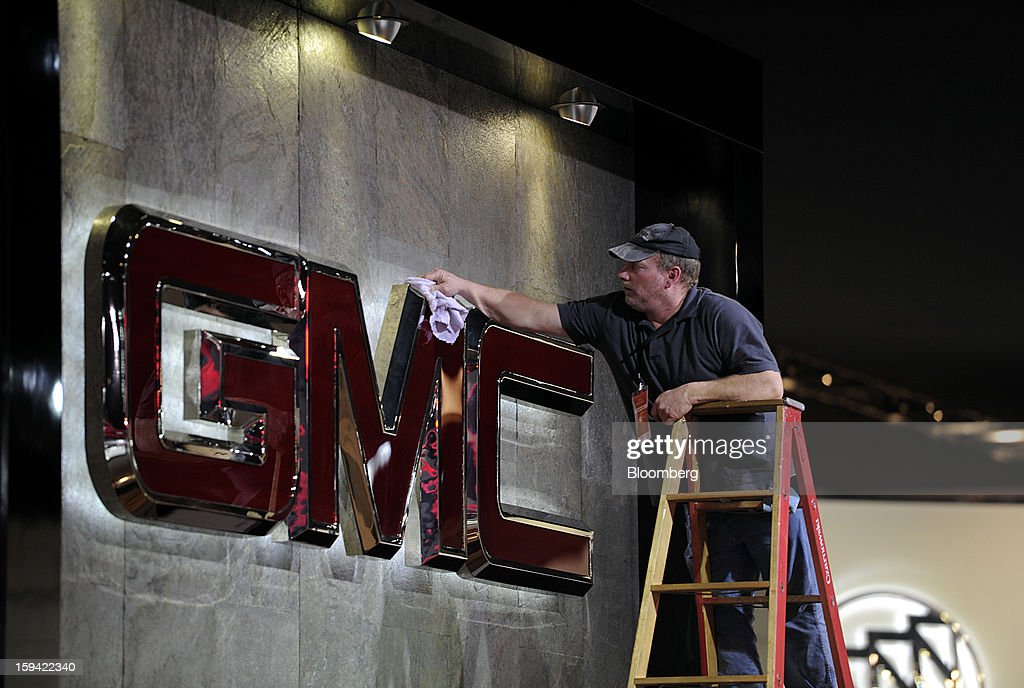 A worker cleans a GMC sign ahead of the 2013 North American International Auto Show (NAIAS) in Detroit, Michigan, U.S., on Sunday, Jan. 13, 2013. The Detroit auto show runs through Jan. 27 and will display over 500 vehicles, representing the most innovative designs in the world. Photographer: David Paul Morris/Bloomberg via Getty Images