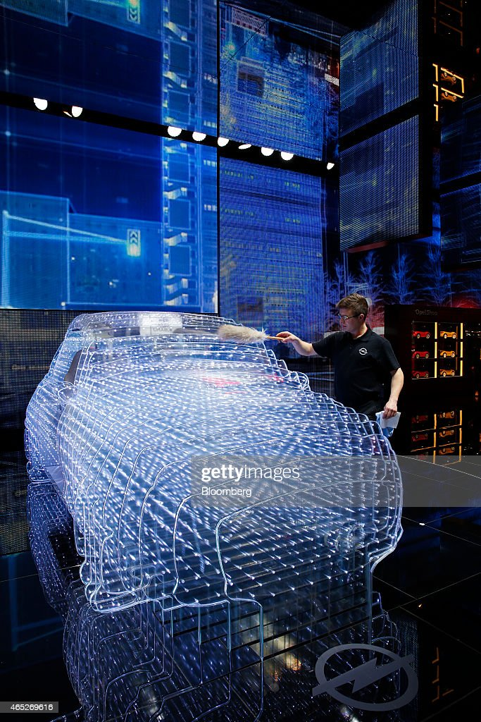 A worker cleans a light installation in the shape of a car as it stands on the Opel OnStar display Adam Opel AG's incar connected app technology on...