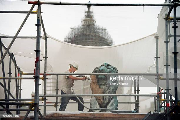 A worker cleans a lion statue as part of the restoration of the Ulysses S Grant Memorial July 13 2015