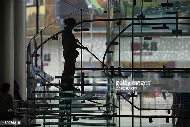 A worker cleans a perspex staircase at an Apple store in Beijing on August 5 2015 AFP PHOTO / GREG BAKER
