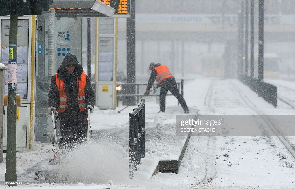 A worker cleans a sidewalks during a snowfall on March 10, 2013 in Berlin.