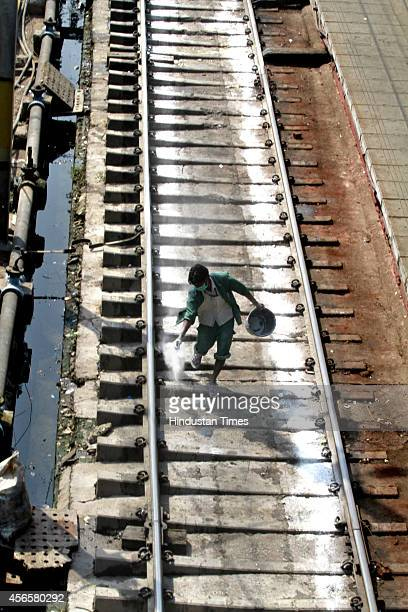 A worker cleans a train track as part of Clean India Drive at Railway Station on October 2 2014 in New Delhi India Prime Minister Narendra Modi...