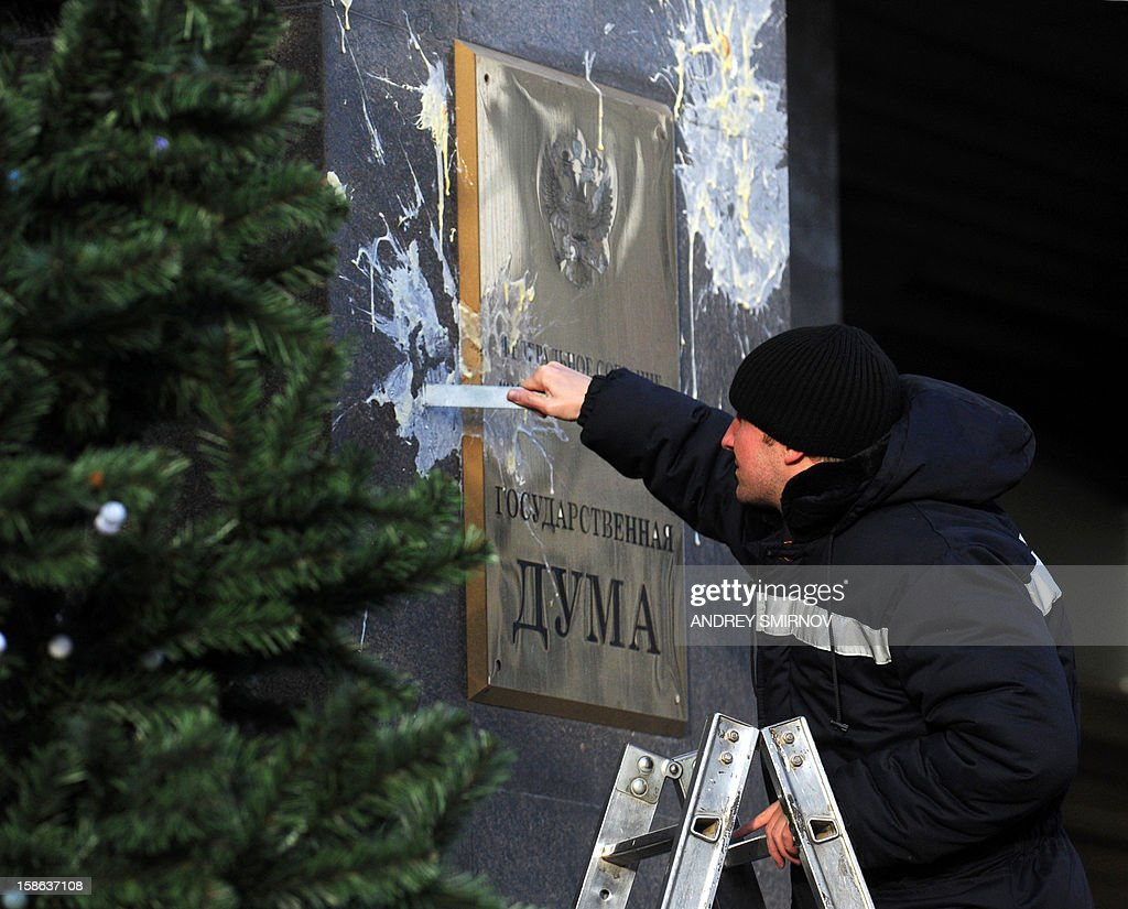 A worker cleans a wall of the State Duma after protesters threw eggs on it, in Moscow, on December 22, 2012. Russia's lower house of parliament has given final approval to a contentious bill that retaliates against a new US human rights measure by barring Americans from adopting the country's children. AFP PHOTO / ANDREY SMIRNOV