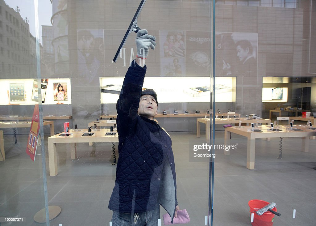 A worker cleans a window at an Apple Inc. store in Shanghai, China, on Tuesday, Jan. 29, 2013. China's economic growth accelerated for the first time in two years as government efforts to revive demand drove a rebound in industrial output, retail sales and the housing market. Photographer: Tomohiro Ohsumi/Bloomberg via Getty Images