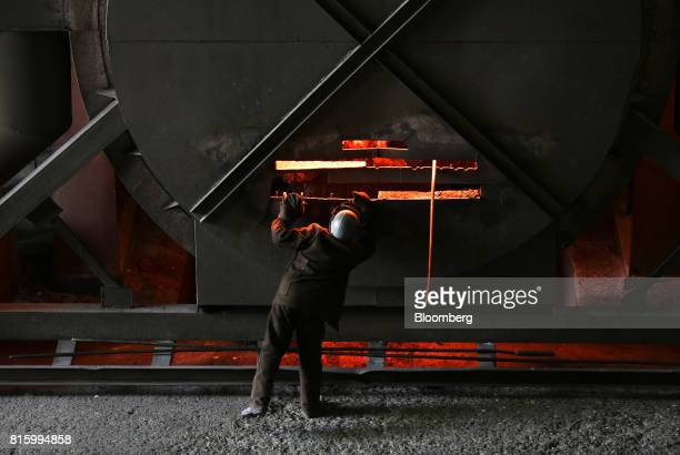 A worker cleans an electric arc furnace in the steel smelting shop at the Oskol Elektrometallurgical Plant steel mill operated by...