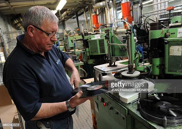 A worker cleans and change a metal device on the production line of vynil at the MPO International company the last French manufacturer in Averton...