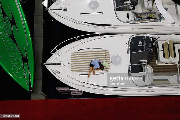 A worker cleans and waxes a boat in preparation for tomorrow's opening day of the Progressive Insurance Miami International Boat Show at the Miami...