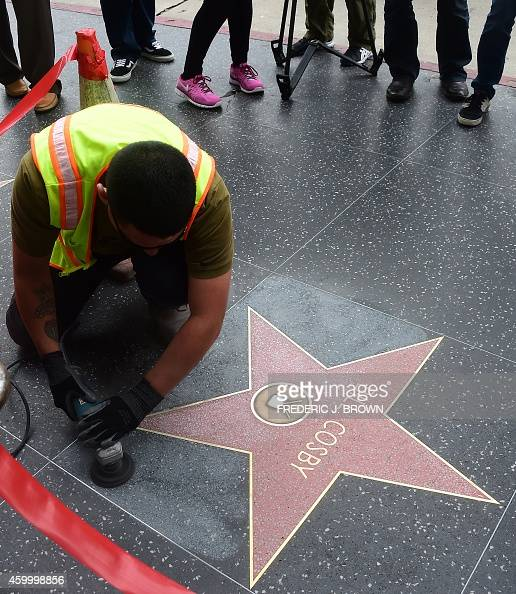 A worker cleans Bill Cosby's Star on the Hollywood Walk of Fame on December 5 2014 in Hollywood California after it was reportedly vandalized the...